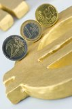 Euro coins. Three Euro coins on a golden Euro-Sign Royalty Free Stock Image