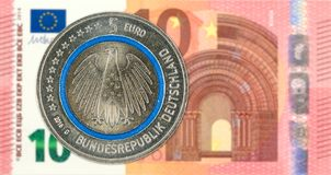 5 euro coins against 10 euro bank note obverse stock photo