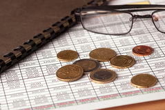 Euro coins and glasses. Euro coins arranged on a financial statement with folder, glasses Stock Image