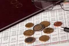 Euro coins and glasses. Euro coins arranged on a financial statement with folder, glasses and pen Royalty Free Stock Images