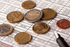 Euro coins and pen. Euro coins arranged on a financial statement with pen Stock Image