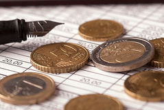 Euro coins and pen. Euro coins arranged on a financial statement with pen Royalty Free Stock Images