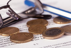Euro coins close up. Euro coins arranged on a financial statement with pen and glasses Stock Photography
