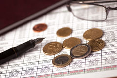 Euro coins and pen. Euro coins arranged on a financial statement with pen, glasses and folder Royalty Free Stock Photo