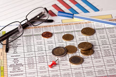 Euro coins and glasses. Euro coins arranged on a financial statement with pen and glasses - still life Royalty Free Stock Photography
