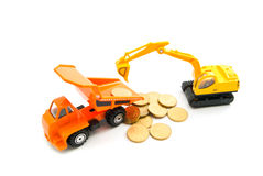 Euro coins, backhoe and orange truck Stock Images