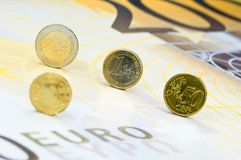Euro coins on banknote. Four Euro-coins rolling over a 200-Euro-banknote Stock Photos