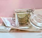 Euro coins and banknotes. On pink background royalty free stock photo