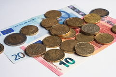 Euro coins and banknotes spread on a white surface. Financial and banking Stock Image
