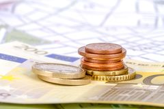 Euro Coins and Banknotes with Touristic Travel Map. Euro coins and banknotes with city map background in touristic travel concept Royalty Free Stock Photography