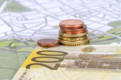 Euro Coins and Banknotes with Touristic Travel Map. Euro coins and banknotes with city map background in touristic travel and finance concept Royalty Free Stock Photo