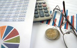 Euro coins with bar chart and pie chart. 2 Euro coins on top of bar chart with calculator and glasses, and pie chart to side with spreadsheet Stock Photos