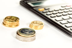Euro coins and calculator in the background. Increment of capital: euro coins and calculator in the background Stock Photos