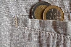 Euro coins with a denomination of 1 and 2 euros in the pocket of worn linen pants. Euro coins with a denomination of one and two euros in the pocket of worn Royalty Free Stock Photo
