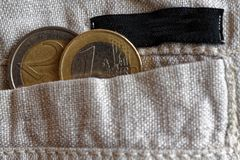 Euro coins with a denomination of 1 and 2 euro in the pocket of linen pants with black stripe. Euro coins with a denomination of one and two euro in the pocket Royalty Free Stock Photos