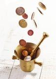 Euro coins falling into mortar and pestle Royalty Free Stock Photos