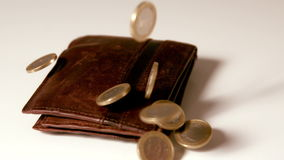 Euro coins falling over brown leather wallet on white surface stock footage
