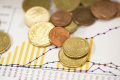 Euro coins on financial data papers stock photos