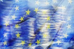 Euro coins and the flag of the European Union. A multiple exposure of some piles of euro coins and a flag of the European Union royalty free stock photography