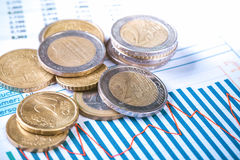 Euro coins on fluctuating graph. Selective focus royalty free stock photo