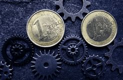 Euro coins with gears. Euro coins and assorted gears - EU economy concept stock photo