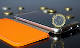 Euro coins and a gold mobile phone in an orange case. Euro money with mobile phone. Euro coins and a gold mobile phone in an orange case Royalty Free Stock Photos