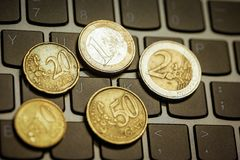 Euro coins on laptop& x27;s keyboard Stock Image