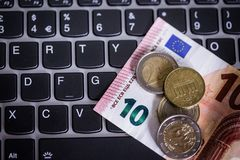 Euro coins and notes on laptop& x27;s keyboard Stock Image