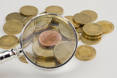 Euro coins and magnifier. Pile of euro coins and magnifier Royalty Free Stock Photography