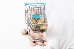 Shopping cart with coins. Euro coins in miniature shopping cart held on open palm against white royalty free stock photos