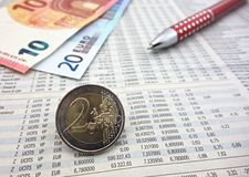 Euro coins. On newspaper and pen macro Stock Image