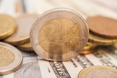 Euro coins over dollars Royalty Free Stock Photo