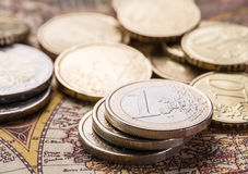 Euro coins over the old world map. Royalty Free Stock Images