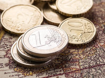 Euro coins over the old world map. Stock Photo