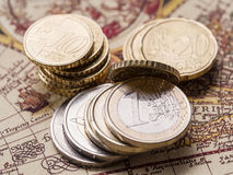 Euro coins over the old world map. Royalty Free Stock Photos