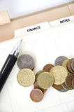 Euro coins with pen on finance page Stock Image