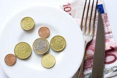 Euro coins on plate fork, knife. Plate with various euro coins, fork and knife lying on 10 euro banknote stock image