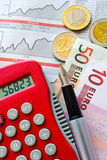 Euro coins and pocket calculator Stock Photography