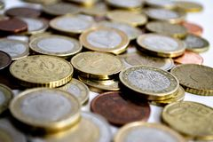 Euro coins of silver and gold scattered on a white background. A large number of coins symbolize wealth, wealth, income and profits. Foreground royalty free stock image