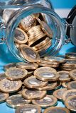Euro coins spilling from jar Stock Photography