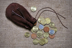 Euro coins spilling out of a drawstring pouch Stock Photos