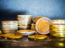 Euro coins on the table. Coin stack with rising chart line, being spotted with scope Stack Euro coins - money royalty free stock image