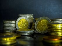 Euro coins on the table. Coin stack with rising chart line, being spotted with scope Stack Euro coins - money stock photography