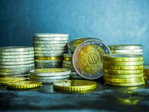 Euro coins on the table. Coin stack with rising chart line, being spotted with scope Stack Euro coins - money royalty free stock photo