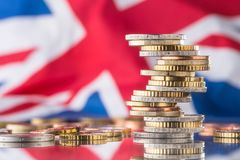 Euro coins an United kingdom flag in the background. Financial c. Oncept Royalty Free Stock Photo