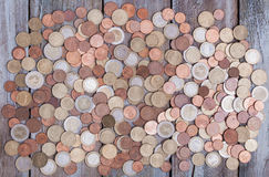 Euro coins on wood board desktop. Large amount of Euro money coins on an aged grunge wood board desktop Royalty Free Stock Photography