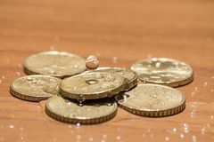 Euro coins on a wood table and a splash of water. Composition Royalty Free Stock Images
