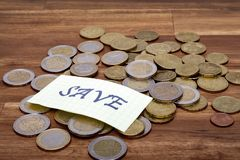 Euro coins with the word save on the table. On the table stock photography