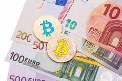 Euro contant geld op witte die achtergrond met twee bitcoins wordt behandeld Stock Foto