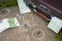 Euro And Crime Scene. Crime scene with handgun cartridges outlines and european currency banknotes spread out on the ground royalty free stock photography